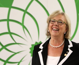 Green Party leader Elizabeth May, smiles as she watches the Globe and Mail leaders' debate on television in Victoria, B.C., on Thursday, September 17, 2015. The Green party leader wasn't invited to the Calgary event hosted by the Globe and Mail newspaper, but she's using Twitter to try to elbow her way into the conversation.THE CANADIAN PRESS/Chad Hipolito